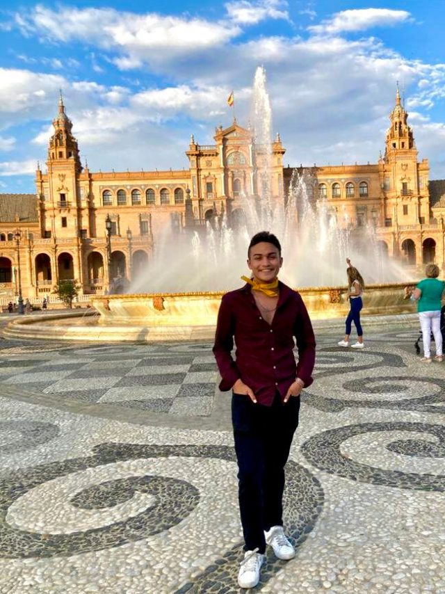 Student in front of fountain at Plaza de Espana in Seville, Spain.