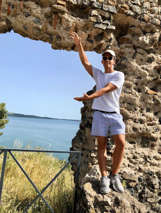 Student standing in front of Lake Bracciano in Italy, doing Gator Chomp