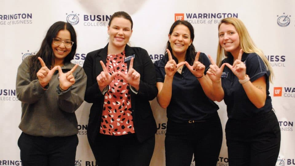 Four female Warrington Welcome students holding their fingers in the shape of a W