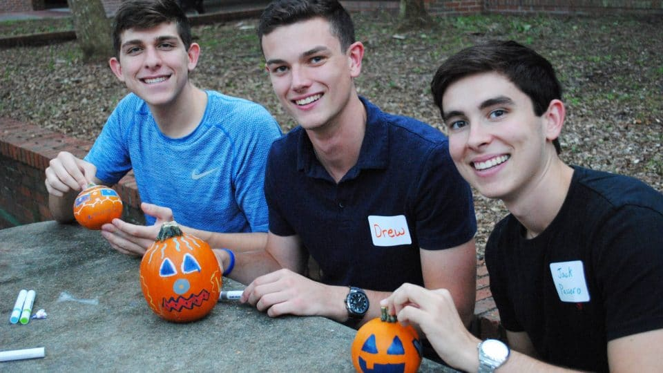 Three male Warrington Welcome students decorating pumpkins with markers